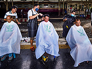 12 SEPTEMBER 2018 - BANGKOK, THAILAND: Travelers get free haircuts at Hua Lamphong train station in Bangkok. Barber schools set up in the station and offer free haircuts to travelers.     PHOTO BY JACK KURTZ