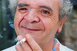 Portrait of man with learning disability smoking cigarette and smiling,