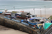 NEWQUAY, CORNWALL, UK - NOVEMBER 17, 2016: Views of Newquay Harbour at low tide in Autumn.  Maintenance work is carried out on many boats at the end of the season.