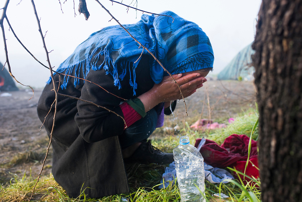 A refugee washes her face at dawn in a refugee camp on the Macedonian (FYROM) border on March 11, 2016 in Idomeni, Greece.