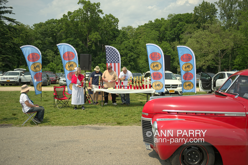 Chevrolet Master Deluxe antique car drives by the trophy table, and ALTHEA TRAVIS, standing at left, dressed in vintage-style white and red nurse's costume, hands out trophies at the 53rd Annual Spring Meet Antique Car Show, sponsored by the Greater NY Region (NYGR) of the Antique Automobile Club of America (AACA), at Old Westbury Gardens, a Long Island Gold Coast estate.