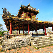 An ornate decorated pagoda outside the walls of the Imperial City in Hue, Vietnam. A self-enclosed and fortified palace, the complex includes the Purple Forbidden City, which was the inner sanctum of the imperial household, as well as temples, courtyards, gardens, and other buildings. Much of the Imperial City was damaged or destroyed during the Vietnam War. It is now designated as a UNESCO World Heritage site.