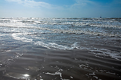 Early morning sunlight on the surf, Spanish Grant development, West Beach, Galveston Island, Texas Gulf Coast.