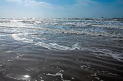 Early morning sunlight on the surf, Spanish Grant development, West Beach, Galveston Island, Texas Gulf Coast.