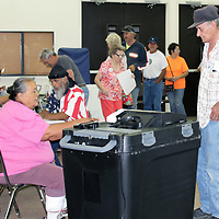 A steady stream of Cibola County voters turned out Tuesday afternoon to cast their ballots in the primary election. Sally Nelson, election clerk, assists a voter as he prepares to submit his ballot, while Leon Price (flag shirt), presiding judge, checks the roll of voters.