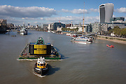 A tug tows a heavy crane downstream on the Thames, passing on the right, the Walkie-Talkie building in the City of London.