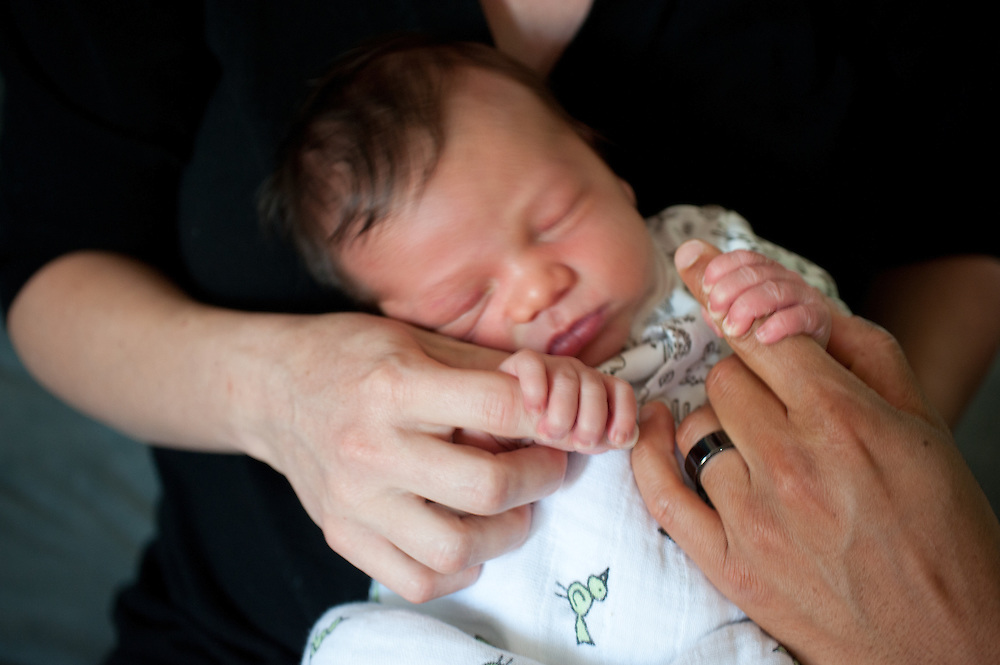 newborn baby holding parents hand