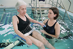Elderly patient being lowered by hoist into hydrotherapy pool speaking to physiotherapist,
