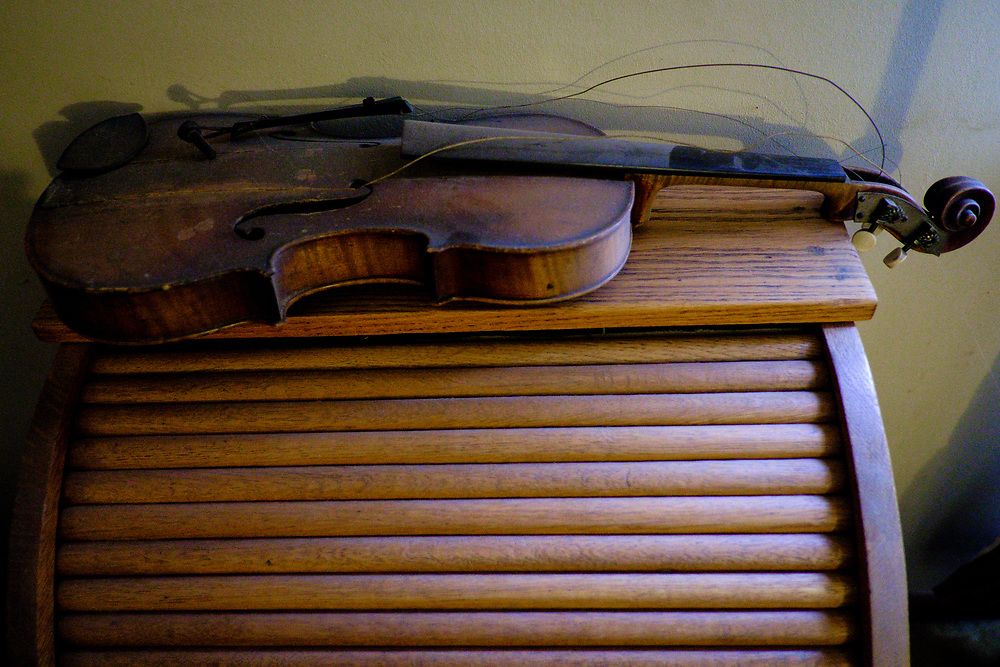 ELKTON, MARYLAND - SEPTEMBER 2: An old fiddle rests on top of Zane Campbell's old school desk in his home in Elkton, Md. on Saturday, September 2, 2017 in Childs, Maryland. Most Campbells are store owners and artists and musicians, including his Aunt Ola Belle, a star of old-time/bluegrass music in the 60s and 70s, who also ran a country-music park. (Photo by Pete Marovich For The Washington Post)