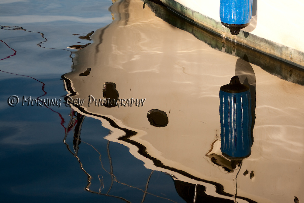 The bow of a boat is reflected in the marina waters at Tarpon Springs' Sponge Docks.