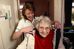 Carer helping an elderly woman with her coat in sheltered accommodation,