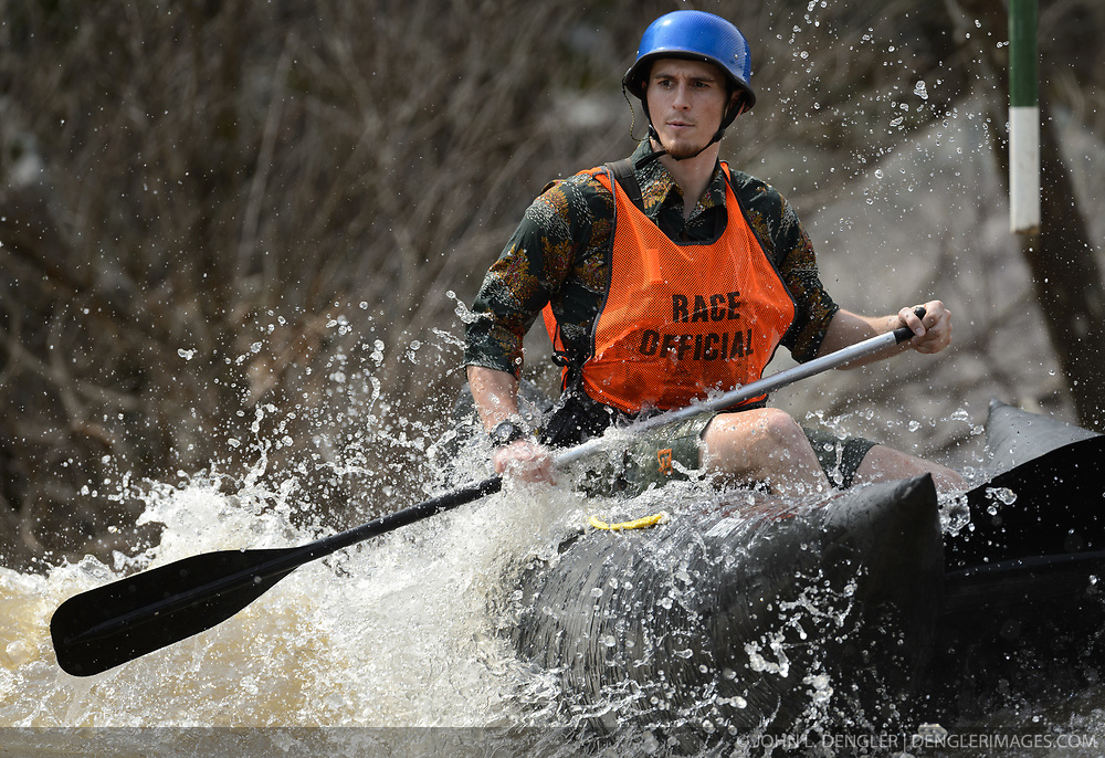 An unidentified race official paddles a raft to his position on the slalom course of the 45th Annual Missouri Whitewater Championships. The Missouri Whitewater Championships, held on the St. Francis River at the Millstream Gardens Conservation Area, is the oldest regional whitewater slalom race in the United States. Heavy rain in the days prior to the competition sent water levels on the St. Francis River to some of the highest heights that the race has ever been run. Only expert classes were run on the flood level race course.
