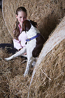 Girl and dog in barn
