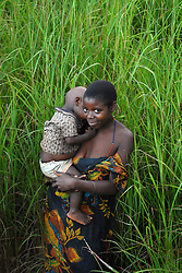 A Tanzanian woman walks through the tall grass with her child near sunset in the village of Simana. The dense forest and tall grasses make villagers vulnerable to lion attacks. They have to stay late in the evening in their fields to protect their crops from rampaging monkeys who like to eat the rice and corn, forcing them to walk at sunset, the time of day when lions are out looking fo prey.  Ami Vitale