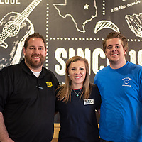 From left to right, Adam Archibale, Anna Connell and Kasey Connell pose for a picture as the new owners of the Dickey's Barbaque Pit in Gallup on Dec. 21, 2018.