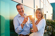 Carefree senior couple enjoy drinks at sunset<br />
