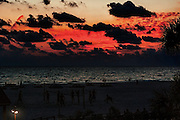 As the light fades over The Gulf of Mexico, a group of guys try to get their volleyball game in before it becomes to dark.