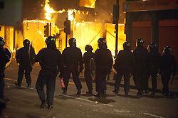 licensed to London News Pictures. London, UK. 7th August 2011. Rioting in Tottenham, London. Police line advances past burning construction site. Violence and looting breaks out from Tottenham High Road after the police shooting of 29-year-old Mark Duggan. Please see special instructions for usage rates. Photo credit should read Jules Mattsson/LNP