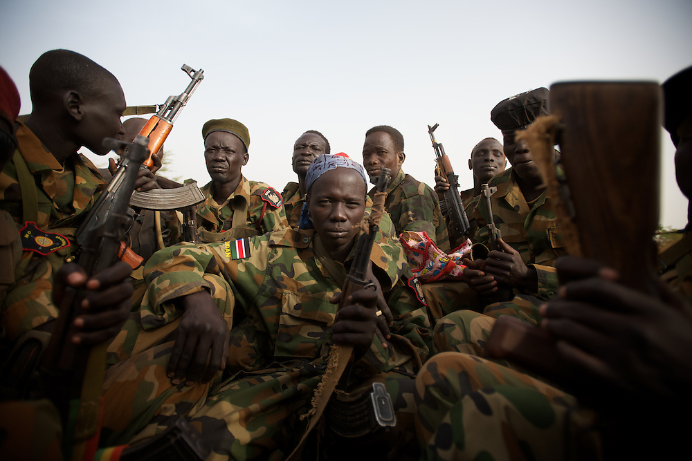 April 24, 2012 - Panakuach, South Sudan: A group of SPLA soldiers riding in the back of a truck in direction to the frontline in near Panakuach village, 70 kilometers north of Bentiu...South Sudan and their northern neighbors, Sudan, have in the past two weeks been involved in heavily clashes over border disputes. Bentiu and neighboring villages have been under constant bombardment by the troops os Karthoum , who established their positions around 10 kilometers into South Sudan's territory. The international community is concerned about the possibility of a full on war between the two countries. (Paulo Nunes dos Santos/Polaris)