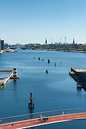 A cyclist riding over a red bridge overlooking the Copenhagen harbour with blue waters and boats.