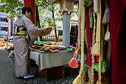 A lady purchases some cloth for kimono, in an open air market that takes place every sunday morning at Hanazono Shinto Shrine in Shinjuku, Tokyo