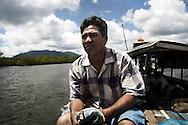 Jao, a Moken fisherman, checks the sea conditions on his boat. Phang Nga province, southern Thailand.