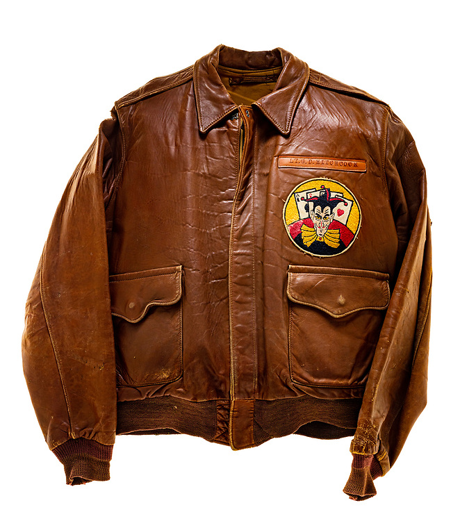 "George D. Hitchcock, a pilot on ""Ole Blood N Guts"", wore this type A2 flight jacket. Hitchcock was attached to the 570th squadron of the 390th Bomb Group. The 570th squadron insignia patch, a joker with 4 aces laid behind it, is sewn onto the front left of the jacket. Above the squadron patch is the name plate which reads ""LT. G.D. Hitchcock"". The name ""Ole Blood N Guts"" is painted on the back of the jacket. ""Ole Blood N Guts"" flew 35 successful missions. Its 35th and final mission was to Hamburg, Germany, on December 31st, 1944. The aircraft sustained heavy damage while on the mission and it ran off the end of the runway on its return back to base. ""Ole Blood N Guts"" was salvaged after this mission."