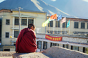 Monk seated on the roof of the Jokhang. //// Moine assis sur le toit du Jokhang.