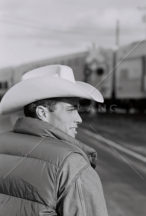 Man in cowboy hat and down vest by a train