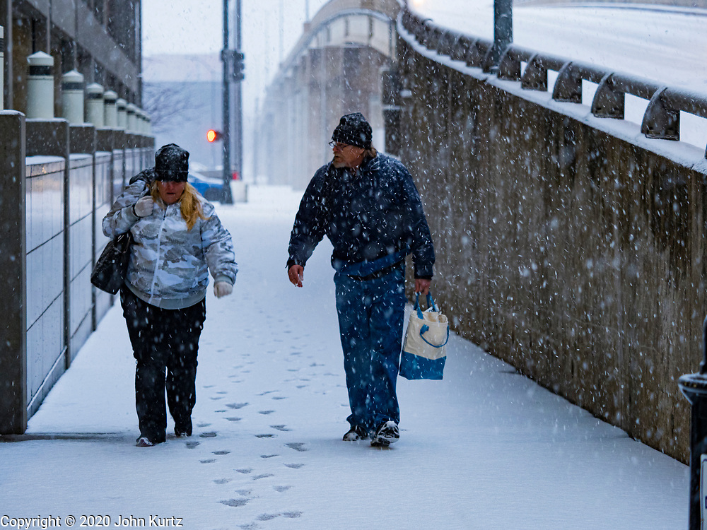 10 JANUARY 2020 - DES MOINES, IOWA: People walk along 8th Street in downtown Des Moines during a snowstorm Friday. The first significant snow in two months blanketed Des Moines Friday evening. Meteorologists are predicting up to six inches of snow overnight and have issued a winter storm warning for southern and central Iowa. Most schools in the affected area closed early and cancelled afternoon events. Some presidential candidates, campaigning ahead of the Iowa Caucuses, cancelled their events.     PHOTO BY JACK KURTZ