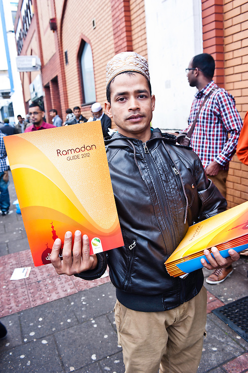 London, UK - 20 July 2012: a man distributes Ramadan Guide 2012 outside the East London Mosque, Britain's largest, right after the celebration of the friday prayer on the first day of Ramadan.