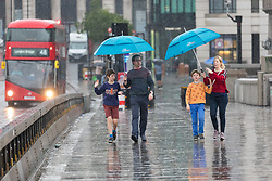 © Licensed to London News Pictures. 27/07/2019. London, UK. A family walk across London Bridge during heavy rain this morning. London and the UK are experiencing heavy rain and stormy weather today following the heatwave and record temperatures during the week. Photo credit: Vickie Flores/LNP