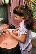 Young girl in pajamas washing her hands before bedtime.