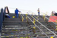 Workers making repairs to the scaffold and planking staircase that links the stadium to the metro station. The staircase has been reported as being wobbly and unstable. Workers were replacing stair treads and welding scaffolding joints. Outside the Maracana Stadium, Rio de Janeiro<br /> Picture by Andrew Tobin/Focus Images Ltd +44 7710 761829<br /> 27/06/2014
