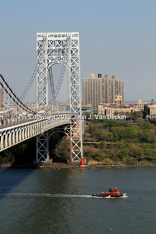 A tugboat heading south on the Hudson River in front of the East Tower of the GW Bridge. George Washington Bridge as seen from Fort Lee, New Jersey, USA