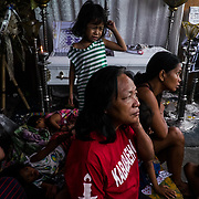 The widow of one of the victims of the drug war lives under a canopy with five children and the sister of the victim waiting to collect the money to bury her husband's body.