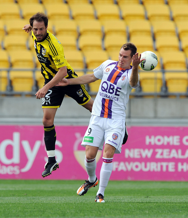 Phoenix's Andrew Durante, left contests the ball with Perth Glory's Shane Smeltz in the A-League football match at Westpac Stadium, Wellington, New Zealand, Saturday, December 10, 2011. Credit:SNPA / Ross Setford