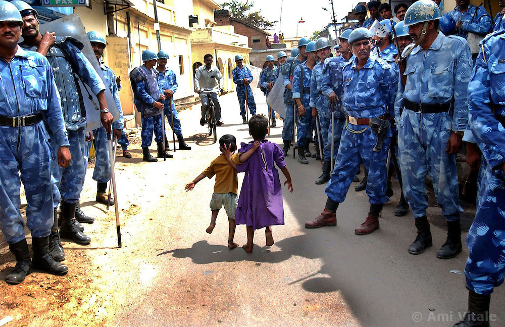 Children run through the streets as the Indian Rapid Action Force conduct a flag in the disputed northern Indian city of Ayodhya, March 14, 2002. The police have sealed the city in anticipation of preventing thousands of kar sewaks or holy men from building a temple  near the site of a razed 16th century mosque that ignited a spree of killing.
