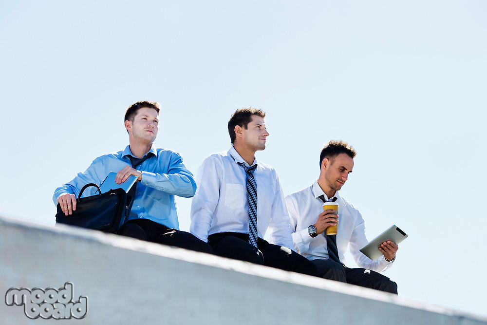 Low angle view of thoughtful mature businessmen sitting and relaxing on rooftop during break in office