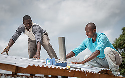 4 June 2019, Meiganga, Cameroon: CAR refugee Moussa Inoussa (right) and Dengui Amadou (left) mount a steel plate as roof of a latrine in the Ngam refugee camp. Supported by the Lutheran World Federation, the Ngam refugee camp, located in the Meiganga municipality, Adamaoua region of Cameroon, hosts 7,228 refugees from the Central African Republic, across 2,088 households.