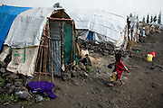 A boy runs back to the hut where he lives with his family in the Mugunga II IDP camp on the outskirts of Goma, Democratic Republic of Congo, on Wednesday December 17, 2008.