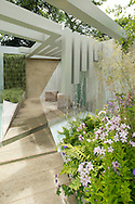 The Garden of Solitude, at the RHS Hampton Court Flower Show 2014. Features include a reclaimed oak seats, a contemporary waterfall, contemporary pergola, and cool pastel coloured plants including campanula, astrantia and digitalis.  East Molesey, Surrey, UK
