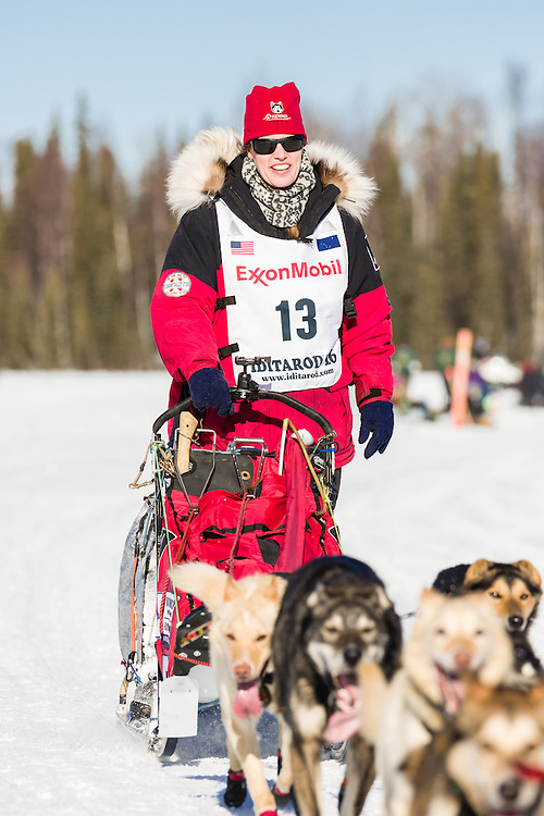 Musher Aliy Zirkle competing in the 44th Iditarod Trail Sled Dog Race on Long Lake after leaving the restart on Willow Lake in Southcentral Alaska.  Afternoon. Winter.