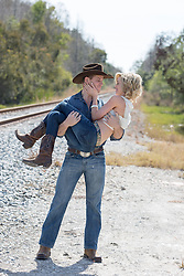 cowboy carrying a beautiful girl near railroad tracks