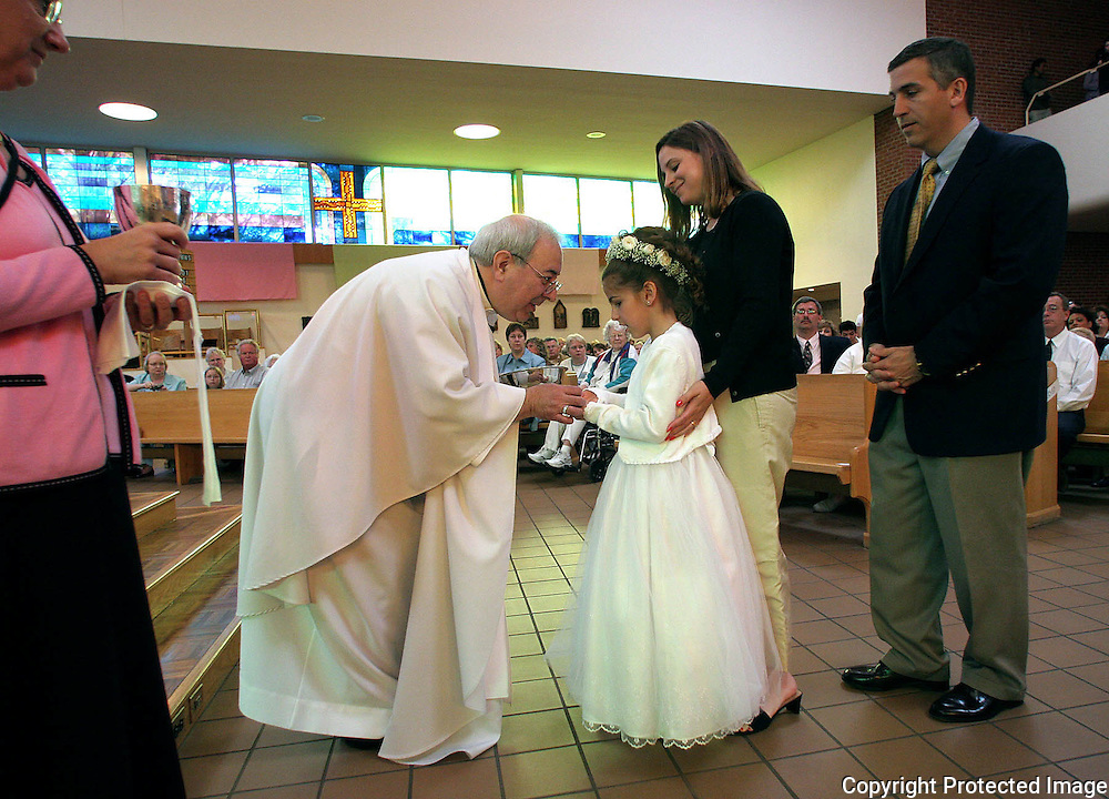 communion - des moines, may 1 --Fr. Anthony Aiello distributes the first Eucharist to Annabelle Costanzo at Holy Trinity Church as parents Gina and Nick Costanzo look on.