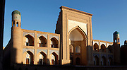 A low angle view of the Qutligh Murad Inaq madrasah, 1804-1812, Khiva, Uzbekistan, pictured on July 6 2010. The sunrise throws strong shadows across the tiered arches of the facade whose shapes echo that of the central Gate. Minarets stand at the corners of the building.