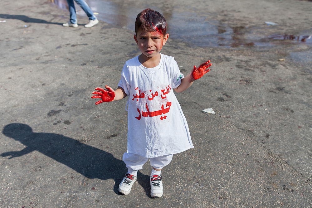 Young shiite muslim boy with a head wound and bloody hands, during the Day of Ashura, Nabatieh, Lebanon (November 14, 2013).