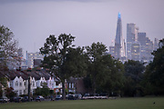 A man walks his dogs in front of south London suburban homes with a background of the Shard tower and City office buildings, in Ruskin Park, Lambeth, on 17th September 2020, in London, England.