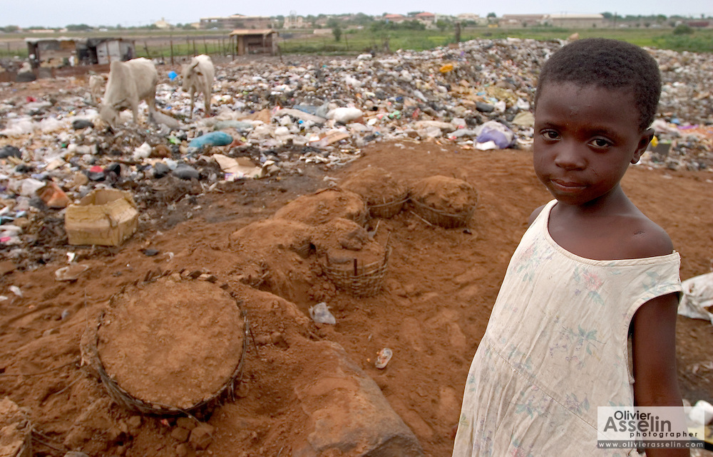 Young girl standing by garbage dump at Ashaiman, one of Ghana's largest slums.