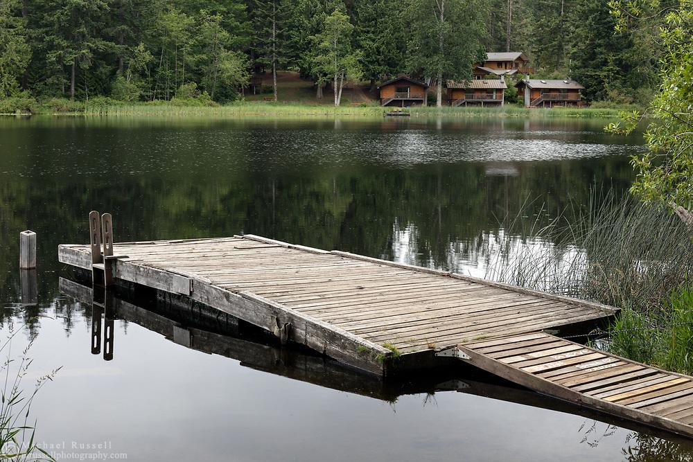 Small swimming and fishing dock (with Cusheon Lake Resort in the background) on Cusheon Lake at the Cusheon Lake Public Viewpoint along Cusheon Lake Road, Salt Spring Island, British Columbia, Canada